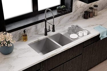 Stainless steel double basin undermount sink with drainboard.