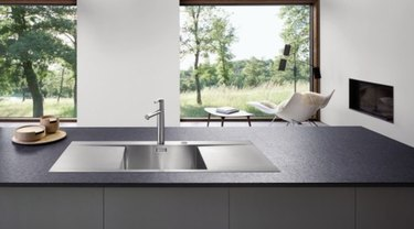 Stainless steel single basin sink on modern kitchen island.