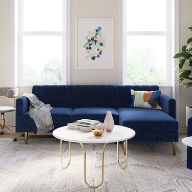 blue sectional sofa near white coffee table with gold legs