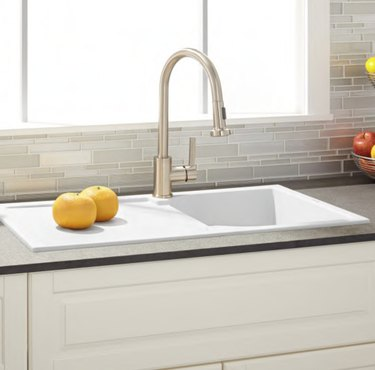 White single basin drop-in drainboard kitchen sink with faucet.
