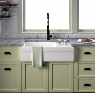 Apron front white sink with light green cabinets, black faucet.