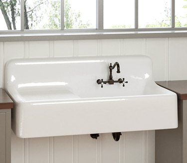White cast iron wall mounted sink with drainboard.