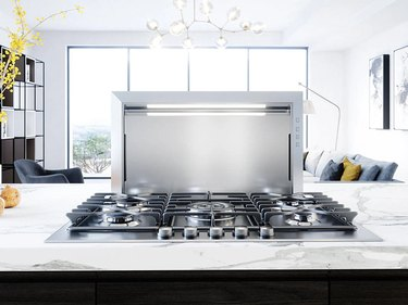 A Zephyr downdraft vent hood on a quartz kitchen countertop with a gas range