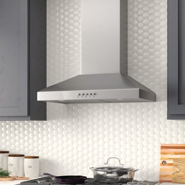 A stainless steel wall-chimney vent hood in a kitchen with a white circular backsplash and gray painted cabinets