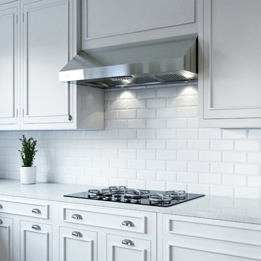 A stainless steel undercabinet vent hood in a white kitchen with a subway tile backsplash