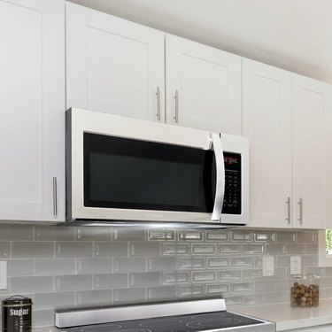 Over-the-range microwave with vent fan in a white kitchen with a gray glass tile backsplash