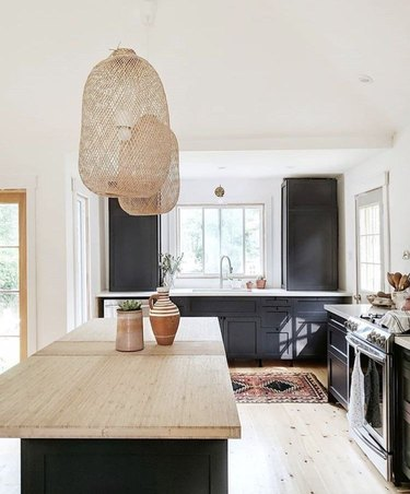 white kitchen with black cabinets and rattan pendants