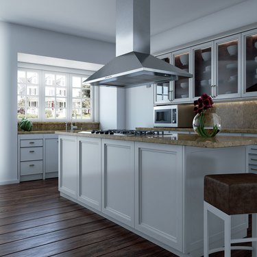 An island vent hood over a white kitchen island with granite countertops
