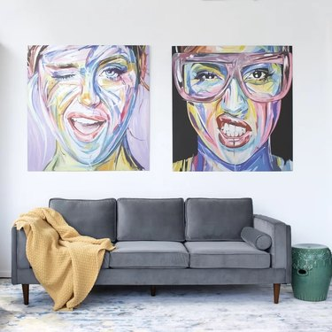 Gray velvet couch with pop art behind
