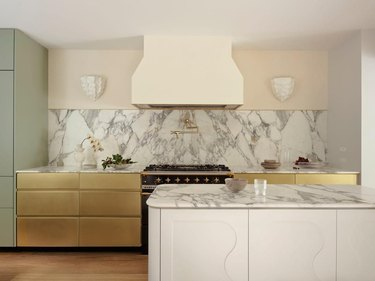kitchen with marble backsplash and brass cabinet fronts