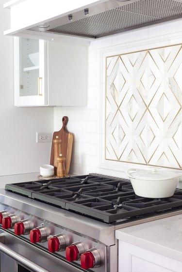 brass and marble backsplash behind stovetop in white kitchen