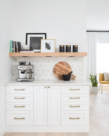 geometric marble and brass backsplash with white cabinets