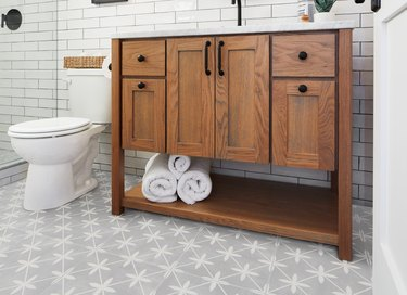 bathroom space with toilet and wood cabinet with towels and tiled floor