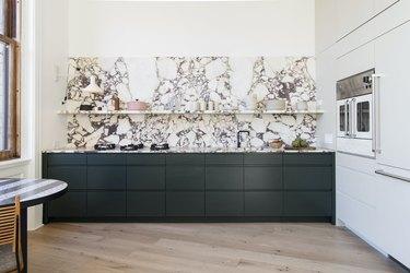marble kitchen backsplash with dark green cabinets