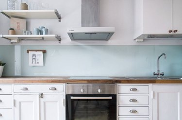 Clear glass backsplash, white cabinets, wood counters, stainless glass top electric stove.