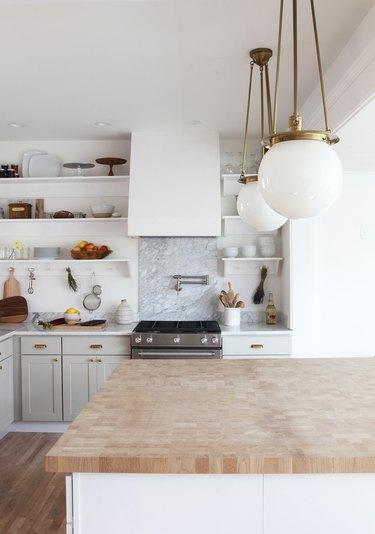 marble backsplash behind stove in white kitchen