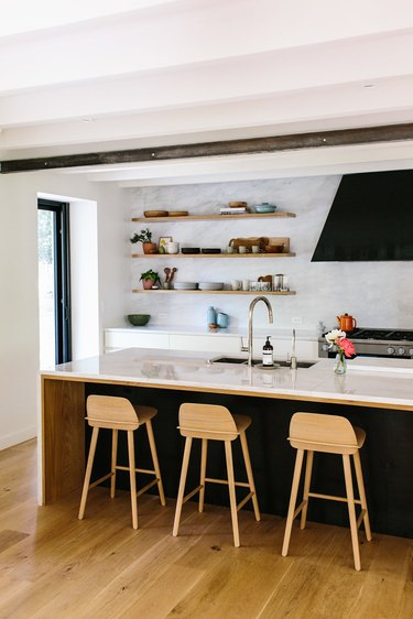marble backsplash and open shelving in a black and white kitchen