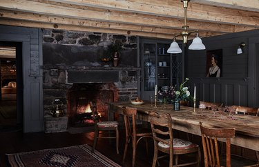 dark rustic dining room with black walls and wooden table
