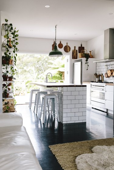 bohemian kitchen with subway tile island and wood countertop