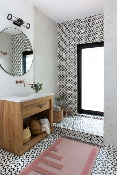 Bathroom with patterned tile and minimal light fixture by Claire Zinnecker Design