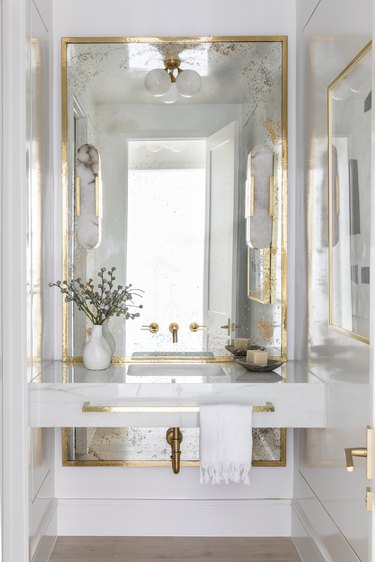 Gold and white bathroom designed by Marie Flanagan Interiors