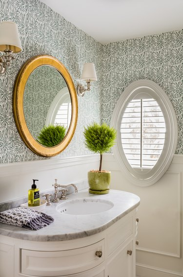 Coastal wallpapered bathroom with minimal light fixtures by KT2 Design Group