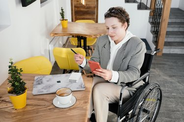 woman in wheelchair at table with laptop and coffee