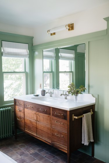 Green bathroom with minimal light fixture by Prospect Refuge Studio