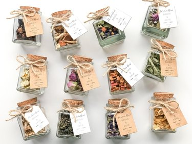 12 small corked jars with different colored tea leaves in them