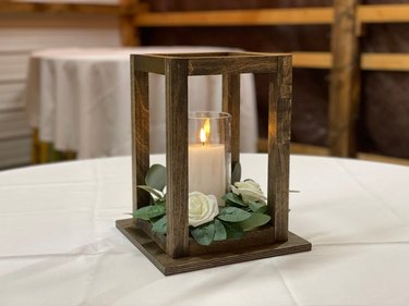 wood lantern centerpiece with greenery and candle