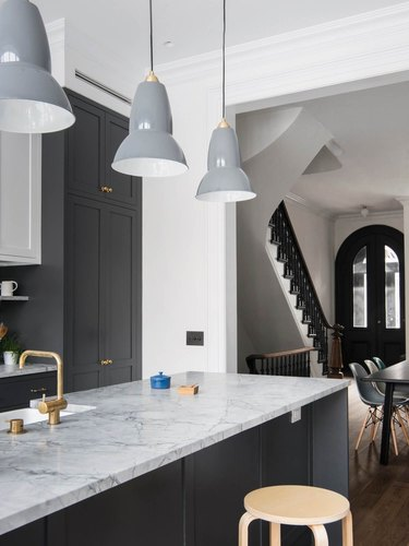 gray and white kitchen with gray pendant lights over island