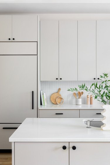 gray and white kitchen with black hardware