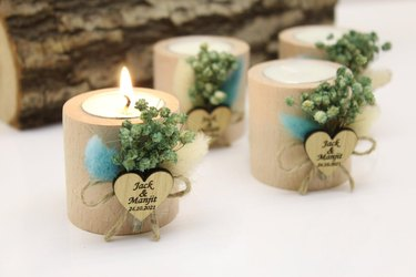 Four beige candles tied with dried flowers and heart-shaped note