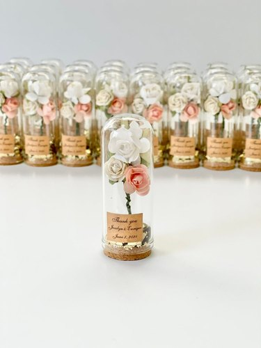 Many small domes with tiny bouquet of artifical flowers and brown tags