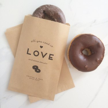 Two brown doughnut bags with the text: all you need is love and some doughnuts