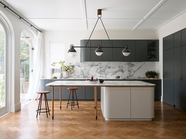 modern gray and white kitchen with marble backsplash and wood flooring
