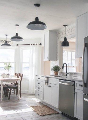 black oversize barn lights in white industrial farmhouse kitchen