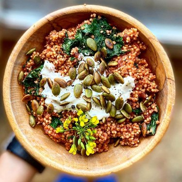 person holding a bowl with grains and veggies