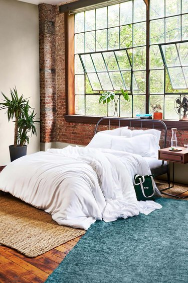 A fluffy white comforter in a bedroom with large windows and rugs.