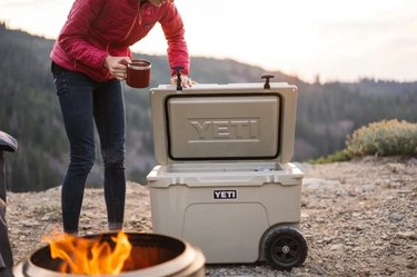 Person fireside with a cooler and mug