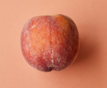 peach fruit on pink background