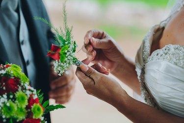bride putting on boutonnière