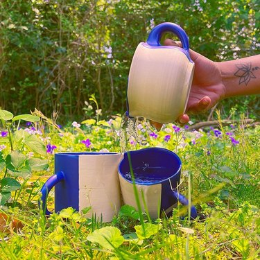 two ceramic mugs in the grass, another mug held by someone's hand on the side