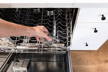 hand reaching for glass in dishwasher