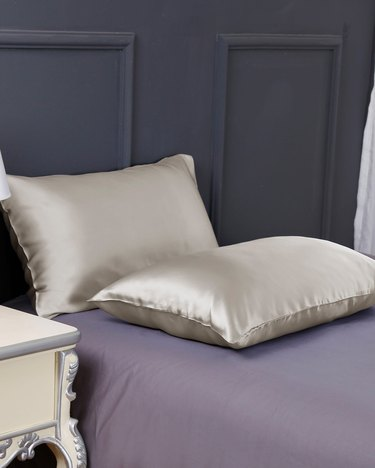 Two silk pillow cases on a purple bed with a navy headboard.