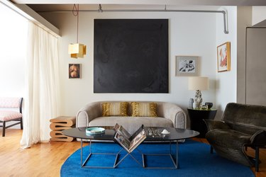 Leyden Lewis living room with blue rug and curved sofa