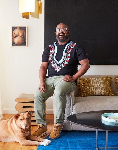 interior designer Leyden Lewis in his living room with dog