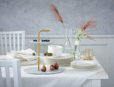 table with white linens and plates and floral decor