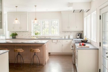 cream kitchen with a wood island and gray countertops