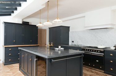 inky blue kitchen with carrara marble backsplash and limestone counters